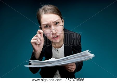 A Young Woman Puts Glasses On Her Nose And Looks In Camera With Angry Surprise. Director Dissatisfie