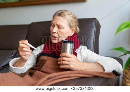 Woman Is Having Flu And She Is Using Thermometer. Sick With A Rhinitis Woman Dripping Nose.