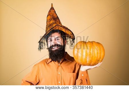 Devil Man. Handsome Man In Halloween Hat Holding Pumpkin - Portrait Close Up. Halloween Man Posing W