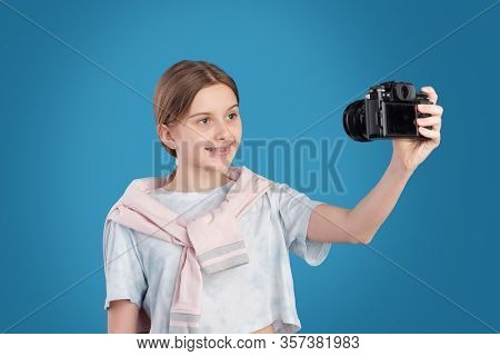 Happy teenage girl in white t-shirt standing against blue background and photographing herself on photocamera in isolation