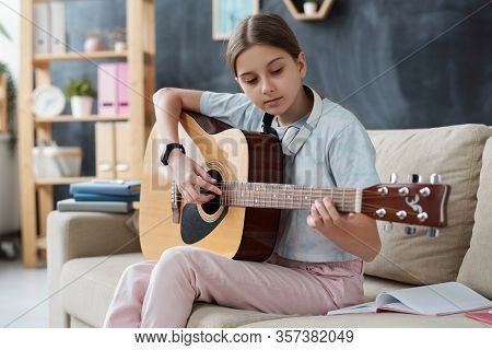 Pretty girl in casualwear sitting on couch and studying to play guitar while taking home lessons during self quarantine