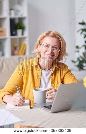 Pretty smiling blond businesswoman in casualwear and eyeglasses looking at you while working at home during self isolation