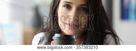 Close-up View Of Beautiful Young Woman Holding Cup With Hot Drink. Smiling Pretty Female With Myster