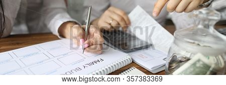 Close-up View Of Couple Calculating Family Budget For New Year. Spouse Accounting Expenses And Plann