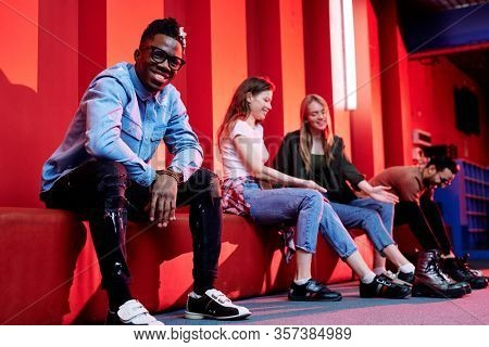 Cheerful young African man in casualwear and bowling shoes looking at you while sitting on background of his happy friends