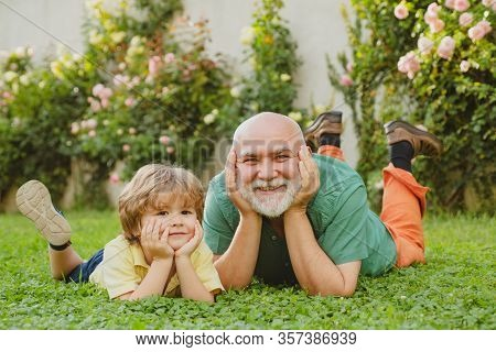 Happy Child With Grandfather Playing Outdoors. Grandfather With Son And Grandson Having Fun In Park.