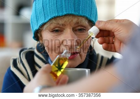 Close-up Of Unhealthy Grandma Holding Cup With Medication. Hand Of Male Person Adding Cannabinoid Oi