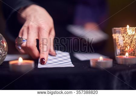 Close-up of fortuneteller's hand with fortune-telling cards at table with candles in dark room
