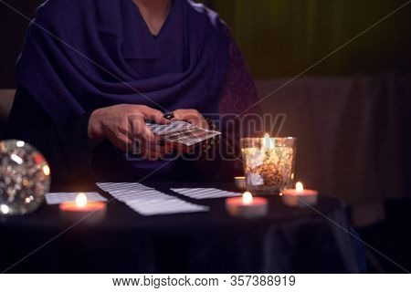 Close-up of soothsayer female guessing on cards sitting at table with burning candles, magic ball