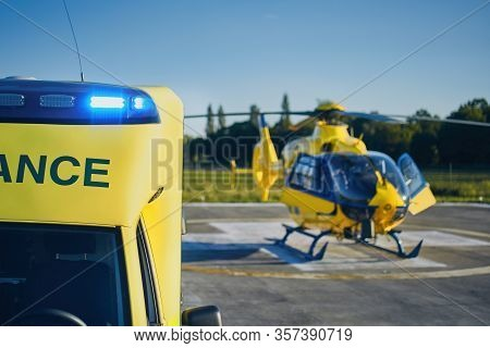Ambulance Car Against Helicopter Of Emergency Medical Service. Selective Focus On Blue Flasher.