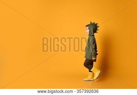 Nice Kid Boy In Hoodie With Dinosaurus Spikes At His Back And Cowl And In Yellow Rubber Boots Wellie