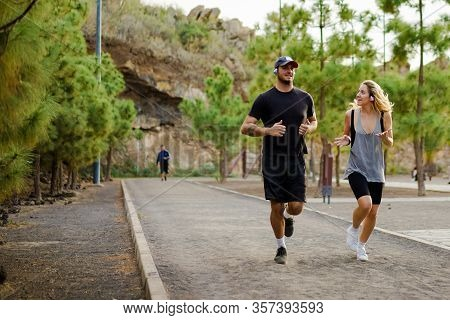 Young People Running Outdoors. Friends Running In The Park. Couple Of Runners On Morning Run. Joggin