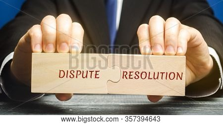 Man Holds Wooden Puzzles With The Words Dispute Resolution. Law And Justice Concept. Litigation, Arb