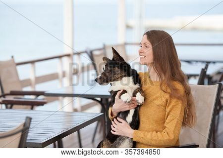 A Beautiful Girl In A Yellow Sweater Is Sitting In A Cafe Holding Her Welsh Corgi Dog Cardigan. Copy