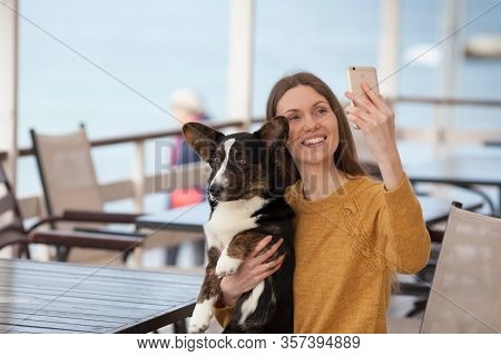 A Beautiful Girl Is Sitting In A Cafe And Holding Her Dog Welsh Corgi Cardigan And Taking A Selfie O