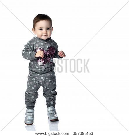 Little Kid In Gray Suit With Snowflakes Print And Boots. She Is Smiling, Stomping On Floor, Isolated
