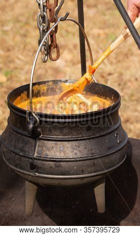 Stew cooking in a potjie cast iron pot over open fire outdoors