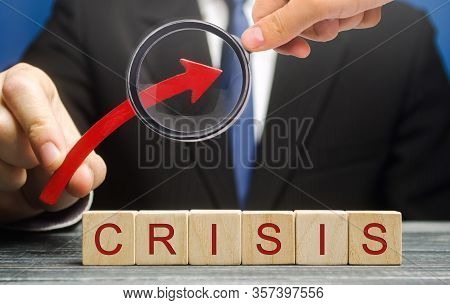 Businessman Holds Up Arrow Over Blocks With The Word Crisis. Increase Instability Of Business And Ec