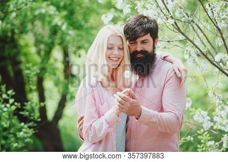 Couple In Love Laughing And Hugging. Couple Enjoying A Moment In Blossoming Garden. Couple In Sunny
