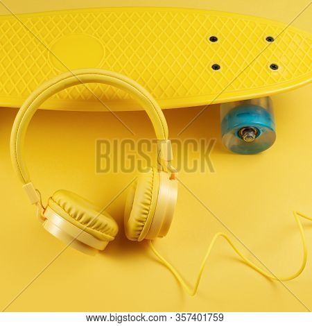 Yellow Headphones And Skateboard Or Pennyboard On Yellow Background. Music Concept.
