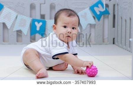 Infant Sitting Play With Ball In Nursery