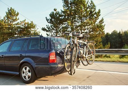 Car Is Transporting Bicycles On Rack. Bikes On The Trunk.
