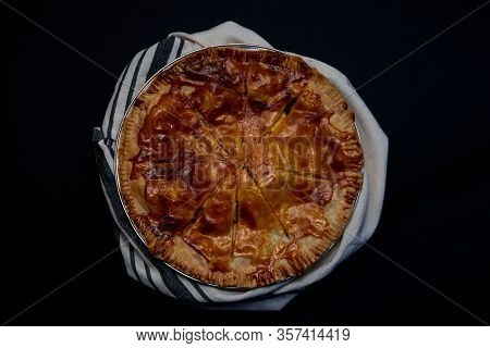 Apple Pie  On Black Background Wraped In Dishcloth Viewed From The Top  -harvest Food Concept