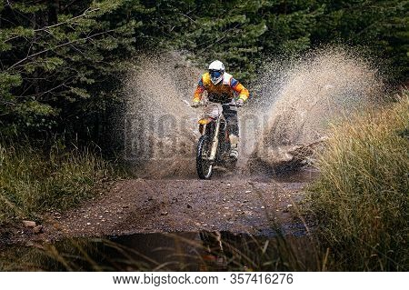 Enduro Racer Riding On Water With Splashes Motocross Race In Forest