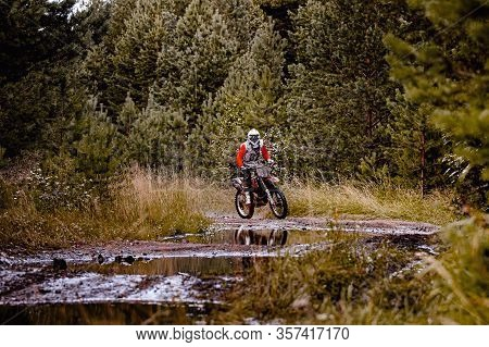 Enduro Racer Riding A Dirty Trail Motocross Race In Forest