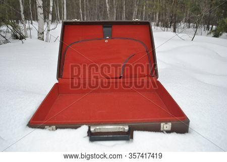 An Open Briefcase Lies On The Snow. Briefcase Close-up. Case Is In The Woods.