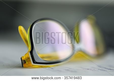 Yellow Plastic Eyeglasses Lying At Worktable Ready To Be Used Close-up