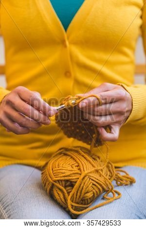 Woman Crochets. Female Hands Close-up. The Girl Is Engaged In Needlework. A Ball Of Yellow Thread An