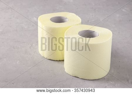 Two Rolls Of Soft Toilet Paper On Gray Background, High Unexpected Demand, Deficit, Covid-19 Pandemi