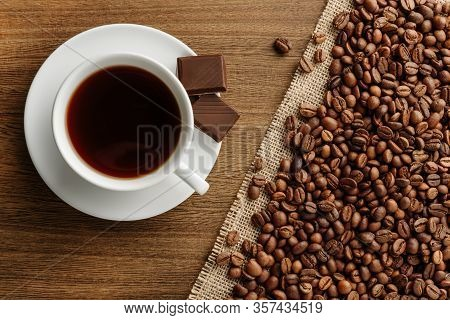 A Cup Of Coffee With Pieces Of Chocolate On A Saucer And Coffee Beans Sprinkled On A Burlap Cloth. C