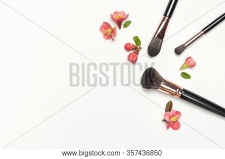 Professional Makeup Brushes With Pink Spring Flowers On Light Gray Background Flat Lay Top View Copy