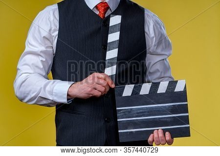 Man With Movie Flap While Filming. Cropped Photo. Film Production. Human Emotions.