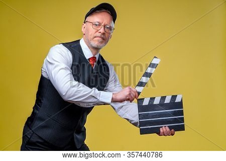 Senior Smiling Director With Movie Flap. Yellow Background. Filming. Film Directing. Film Production