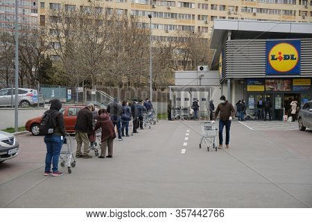Bucharest, Romania - March 24, 2020: People Wait In Line In Front Of A Lidl Supermarket, After A Cor