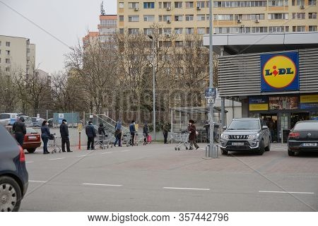 Bucharest, Romania - March 24, 2020: Moderate Queue Of People Wait In Line In Front Of A Lidl Superm