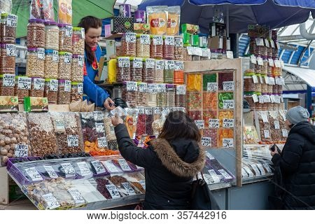 Minsk, Belarus - March 20, 2020: Sale Of Different Sweets, Nuts And Dry Fruits On Market. A Woman Bu