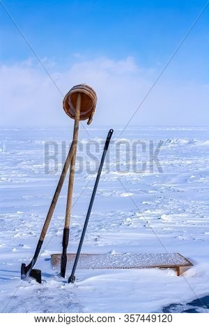 Tools For Punching An Ice Hole In Ice. An Ice Pick, A Shovel And A Bucket Are Stuck In The Ice Hole
