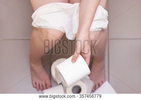 Man Is Sitting On The Toilet. Constipation Or Diarrhea. A Lot Of Toilet Paper On The Floor. Man Hold