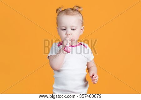 Little Girl About To Blow A Festive Whistle. Portrait Of A Child On A Orange-yellow Background