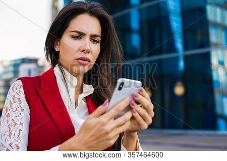 Frustrated Business Woman Received Bad News In E-mail On Mobile Phone While Standing Outside Company