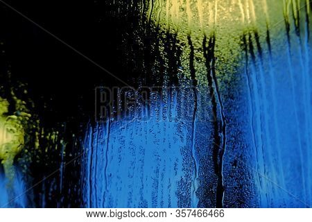 Blurred Many Droplets On A Glass Room With Yellow Blue Light Bulb Glowing In The Dark Night And Blac