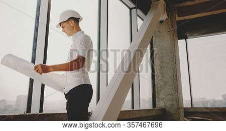 Young Caucasian Man Analysing The Buildings Map While Wearing A Helmet