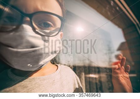 a child in quarantine because of a virus sits at home in a mask and looks out the window on a sunny day.