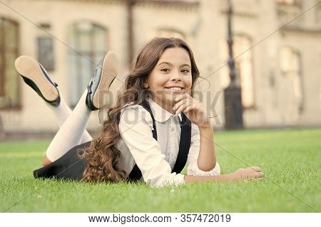 Back To Class And Looking Happy. Happy Little Girl Relax On Green Grass. Cheerful Small Child With H