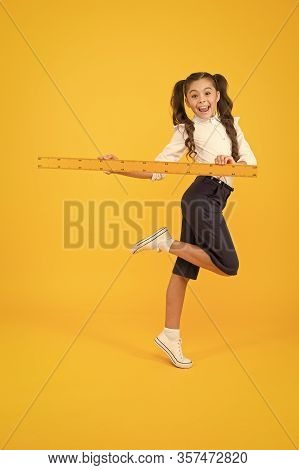 She Is In A Hurry To Lesson. Energetic Schoolchild Holding Long Ruler For Drawing Lesson. Little Gir