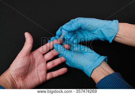 Take Blood From A Finger For Diagnosis. Close-up. On A Black Background. Corona Virus Concept. The D